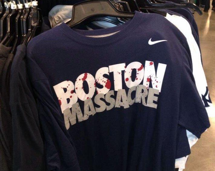 2013 - Nike T-Shirt mit der blutbespritzten Aufschrift Boston Massacre. Dieses T-Shirt wurde schon Wochen vor dem Boston-Marathon-Anschlag in manchen New-Yorker Nike-Outletstores zum Verkauf angeboten.